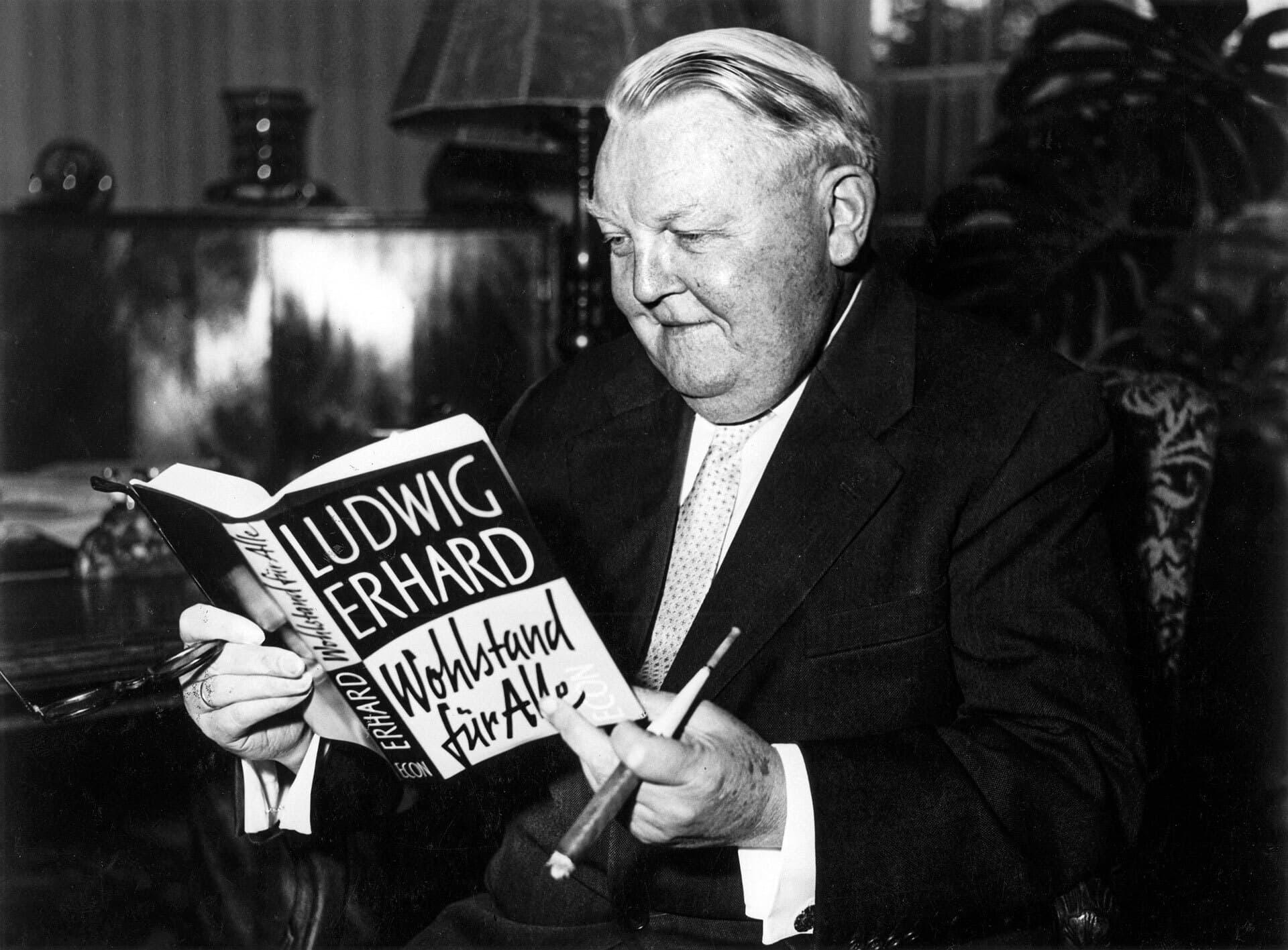 Der Politiker Ludwig Erhard mit einem Buch in der Hand