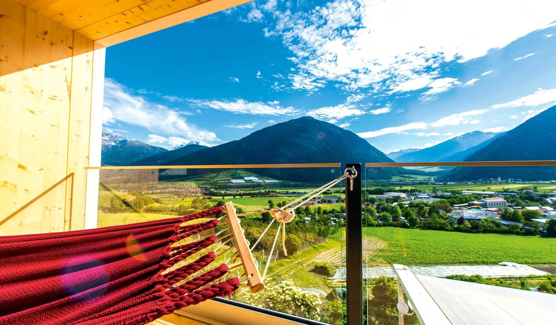 Blick aus einem Hotelzimmer mit Hängematte auf ein Bergpanorama