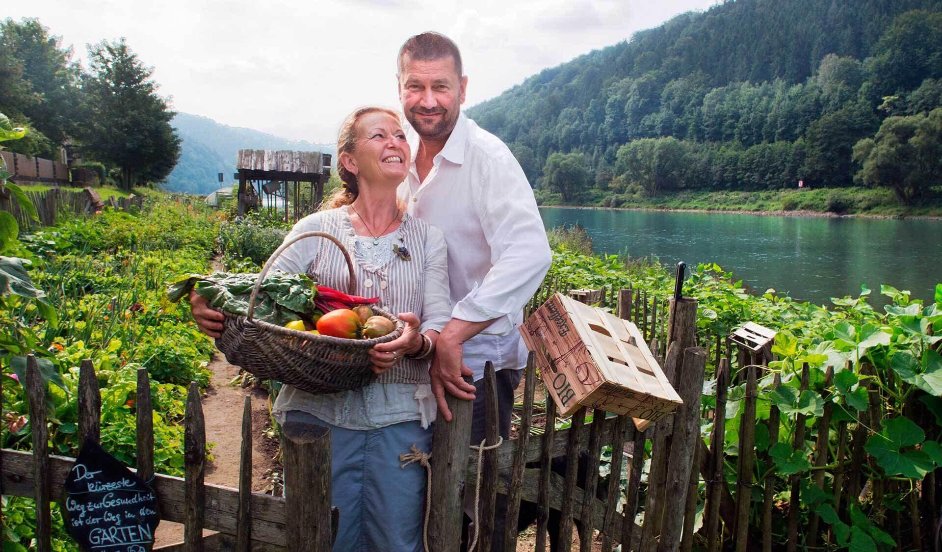 Familie Hitzer steht mit Gemüsekorb vor dem Kräutergarten
