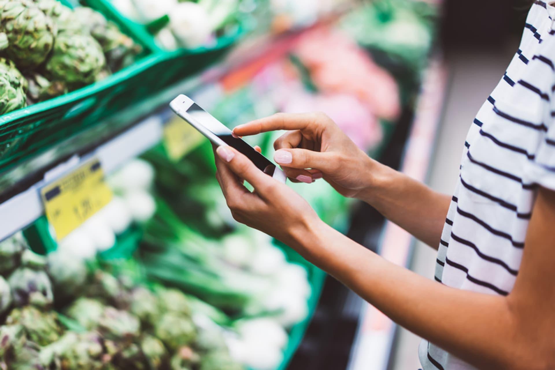 Eine Frau steht vor einem grünen Supermarktregal mit verschiedenen Gemüsesorten und schaut etwas auf ihrem Smartphone nach.