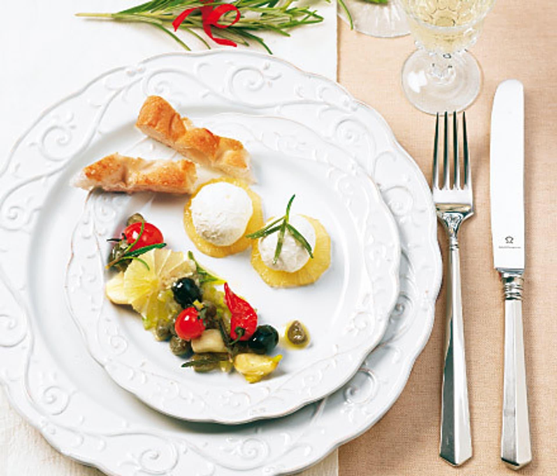 Ein festlicher weißer Teller mit kleinen Happen und einem kleinen Salat belegt
