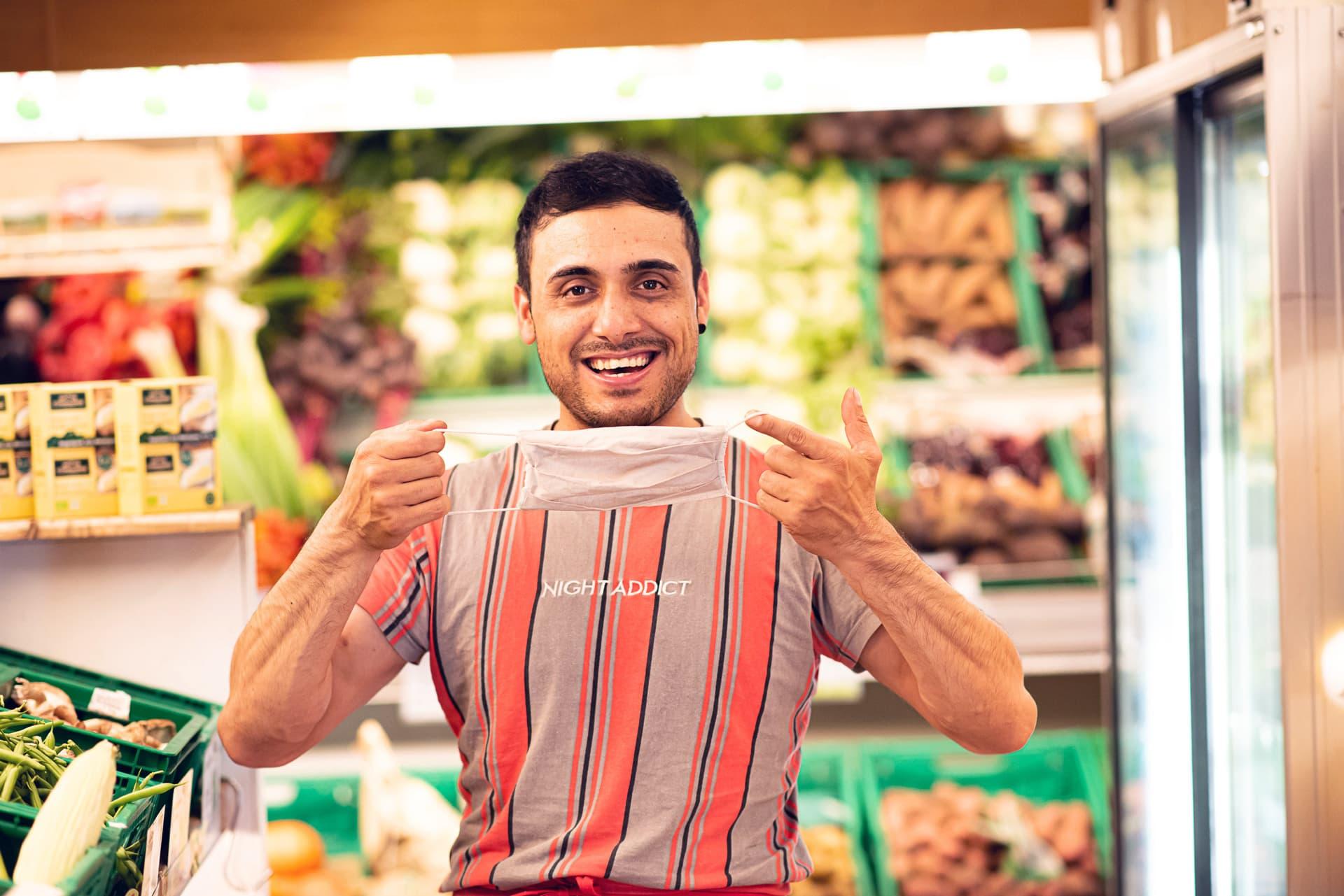 Freundlich lächelnder Bio-Laden-Mitarbeiter mit einer Corona-Maske in der Hand