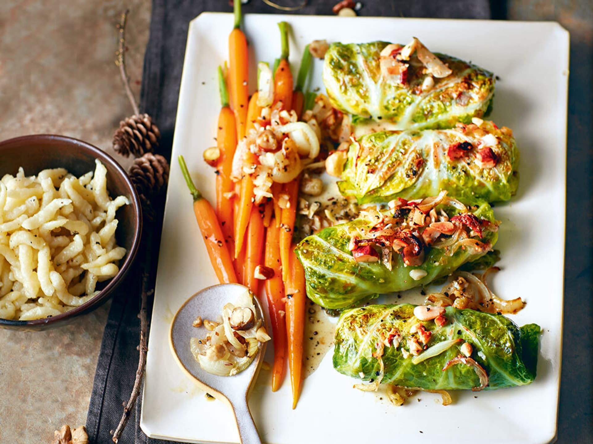 Wirsing-Rouladen mit Karottengemüße und Spätzle auf einem Teller