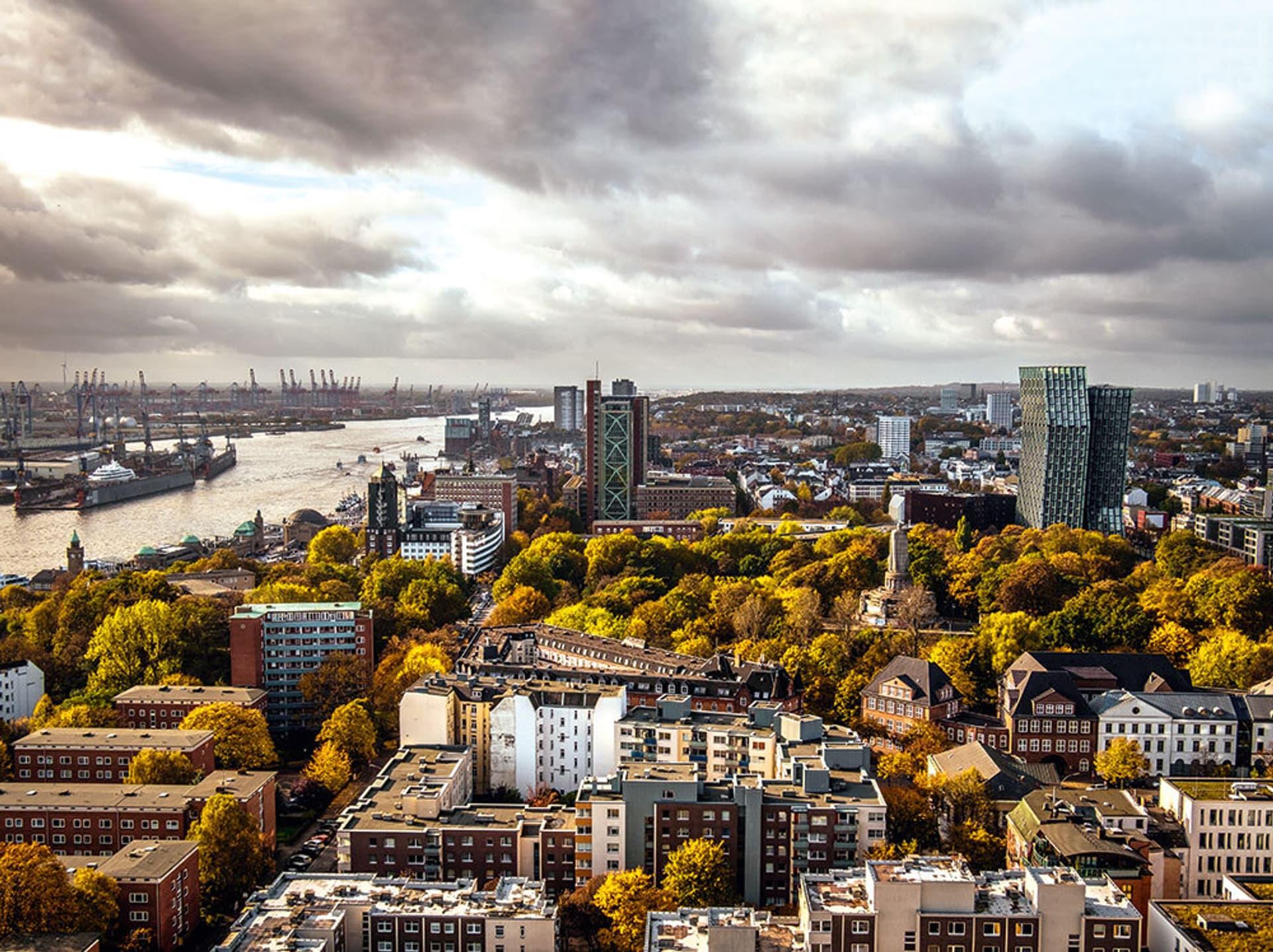 Hamburg von oben: Gebäude, Baumkronen, links die Elbe, wolkenverhangener Himmel
