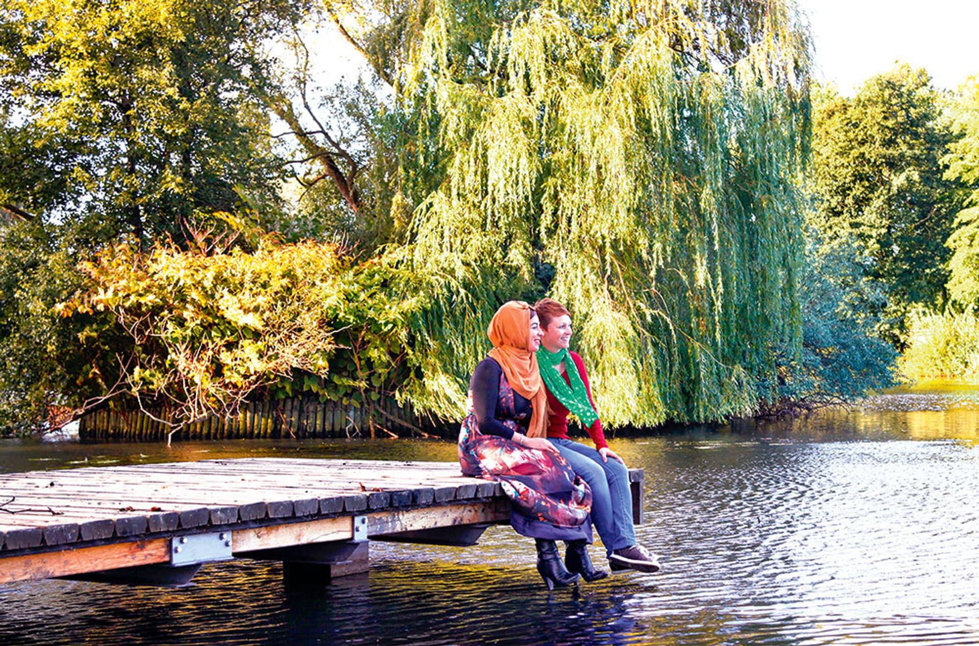 Zwei Frauen sitzen auf einem Holzsteg, der in einen Teich im Park hineinragt. Im Hintergrund Bäume, die am Ufer wachsen