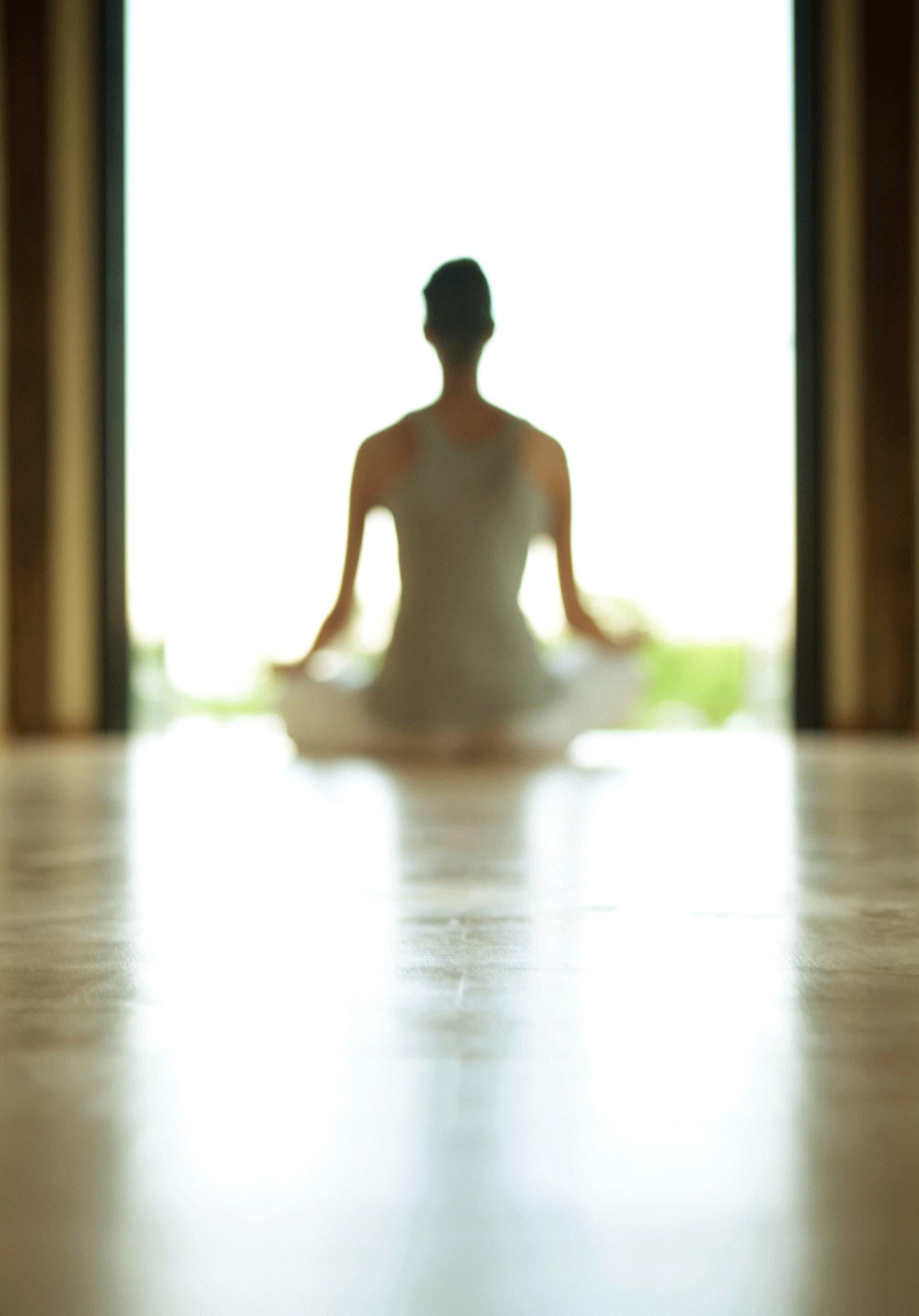 Eine Frau sitzt im Lotussitz vor einem Fenster. Man sieht sie von hinten, das Bild ist verschwommen.