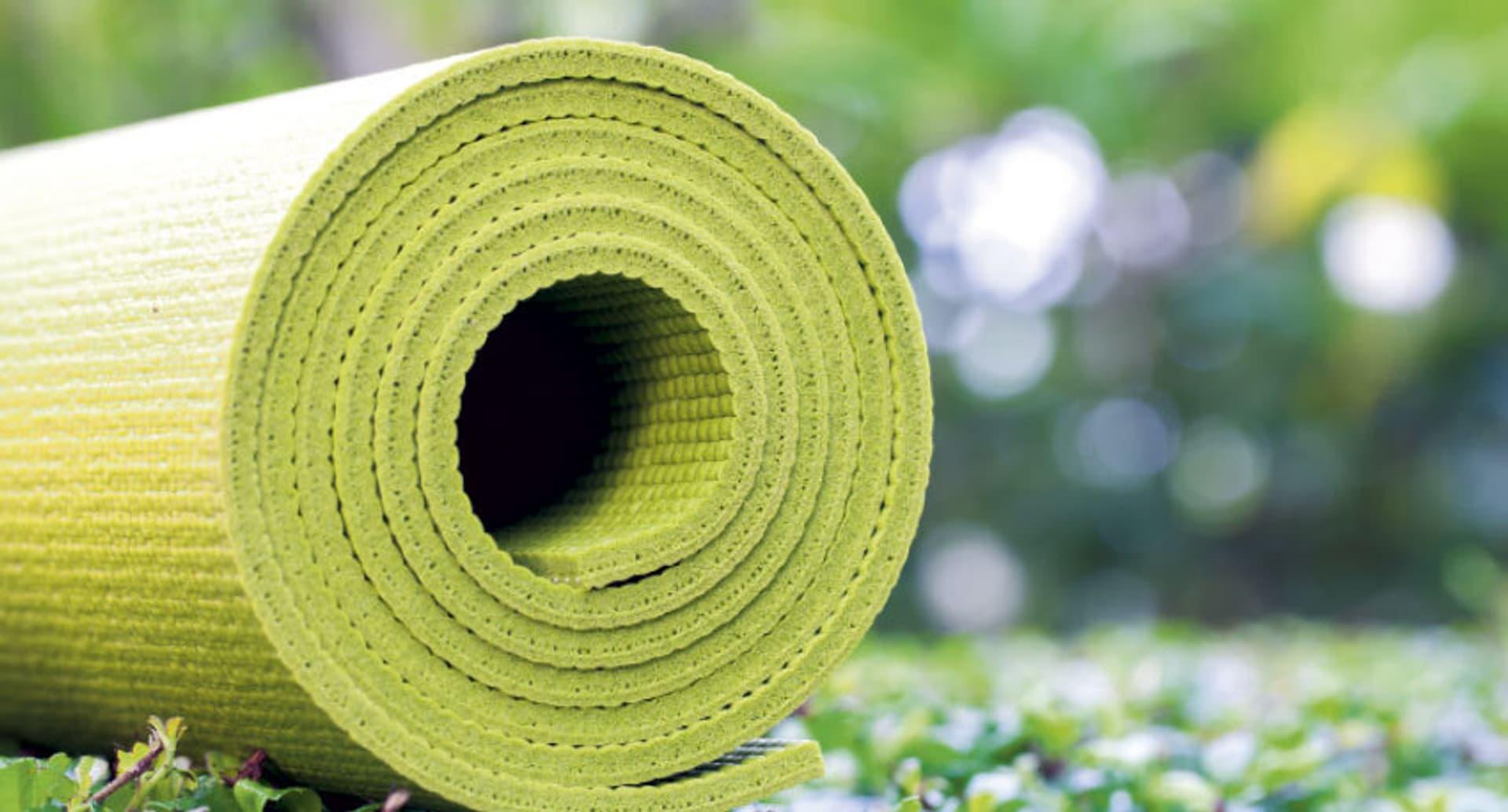 Eine zusammengerollte grüne Yogamatte