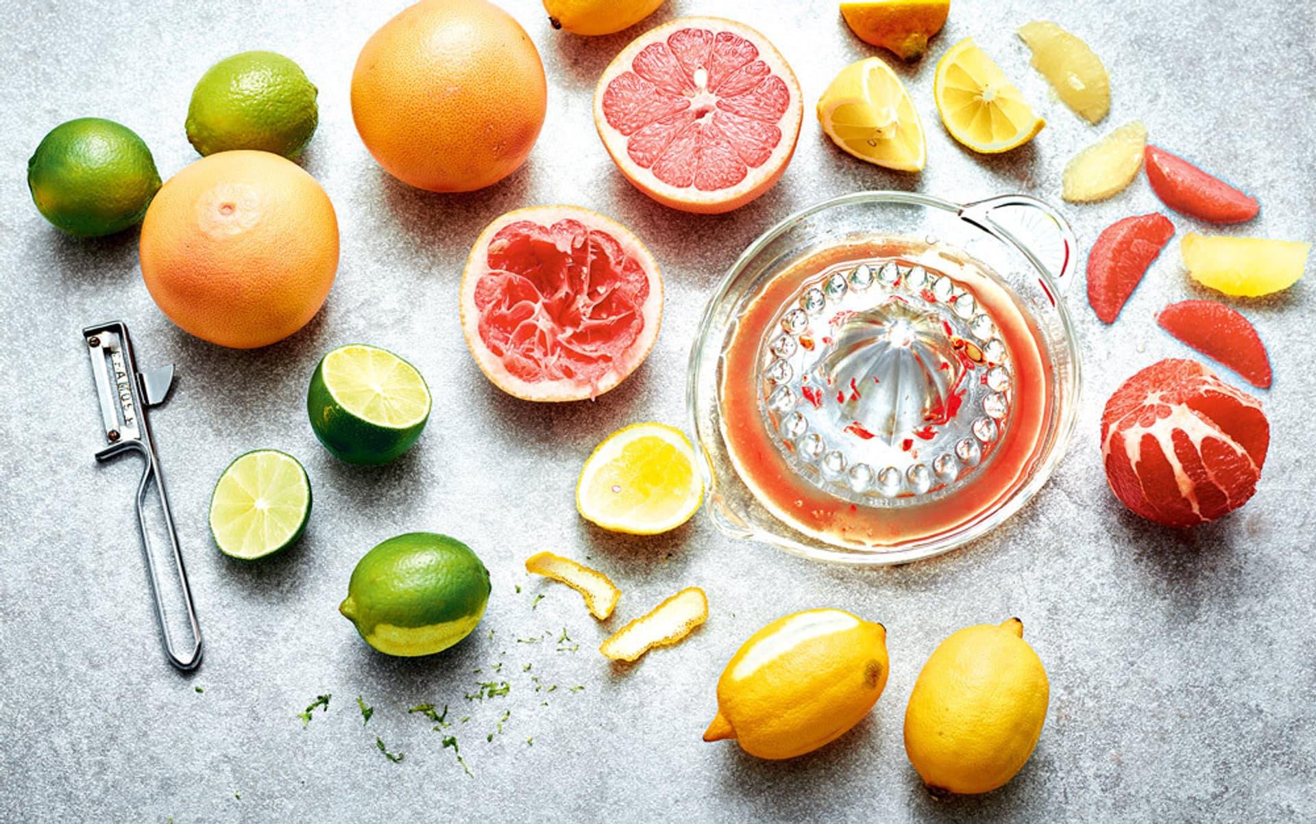 Zitrusfrüchte (Limetten, Grapefruit, Zitronen) auf einer Marmorplatte