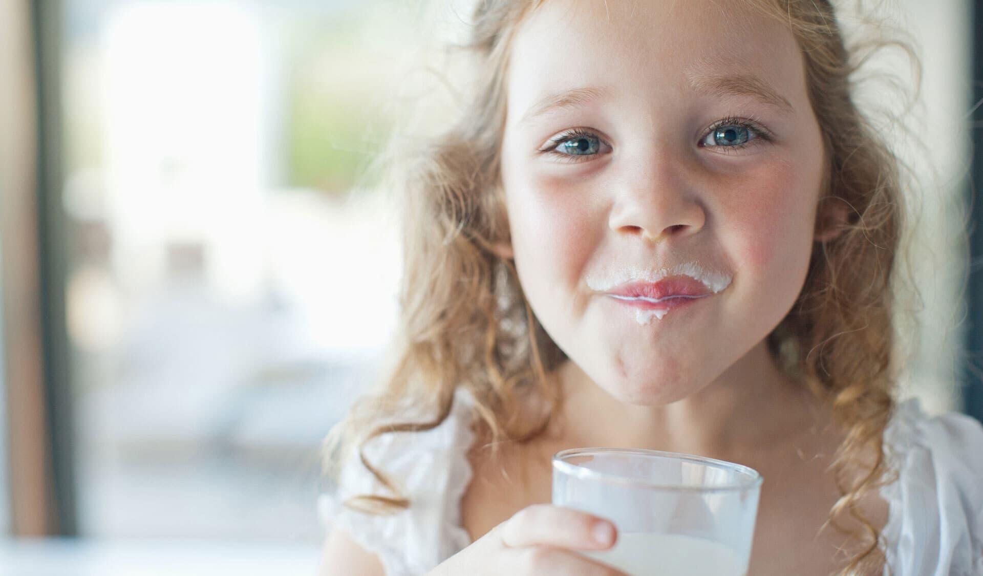 Kleines Mädchen trinkt ein Glas Ziegenmilch