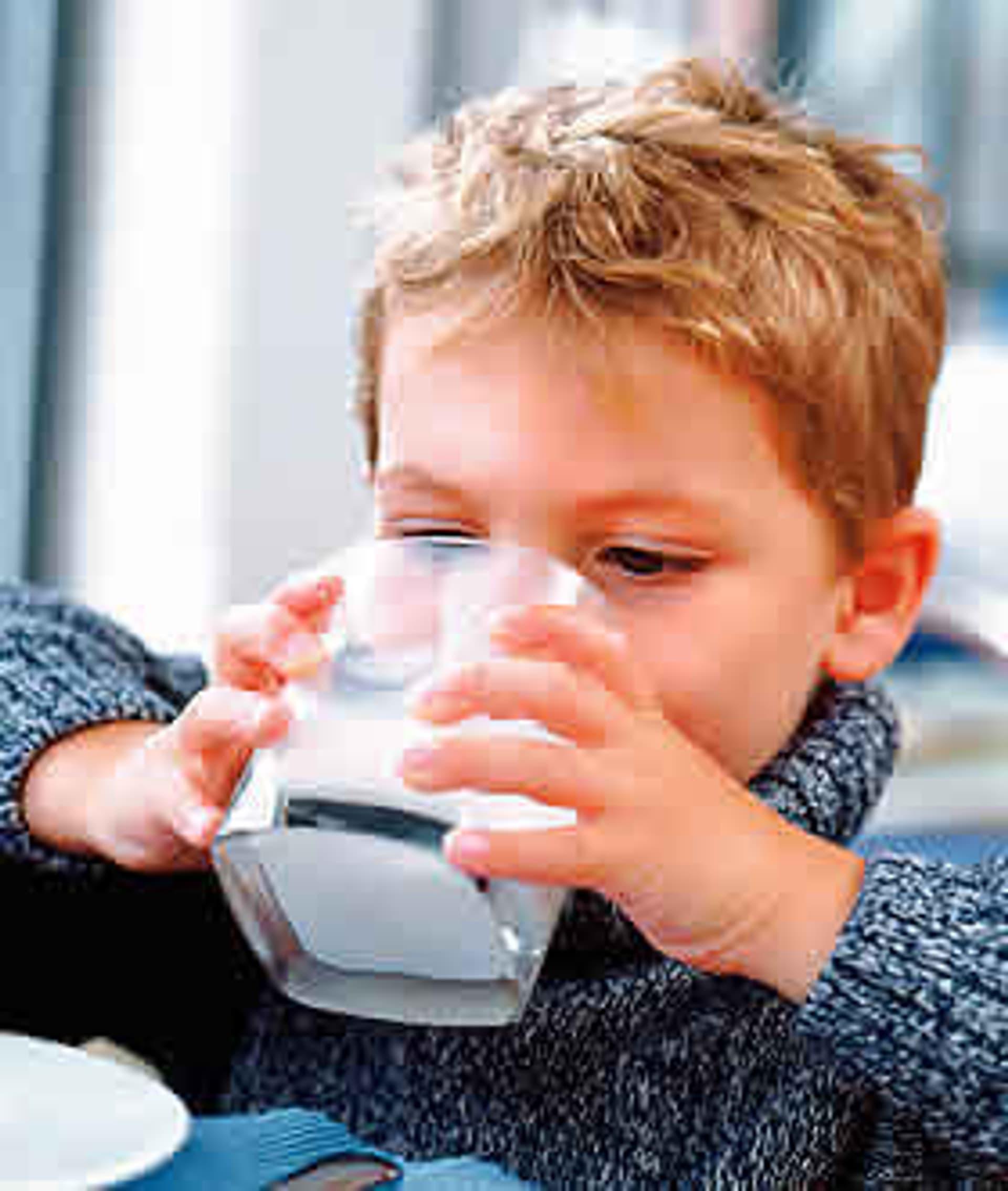 Kleiner Junge hält ein Glas Milch mit beiden Händen und setzt es zum Trinken an.