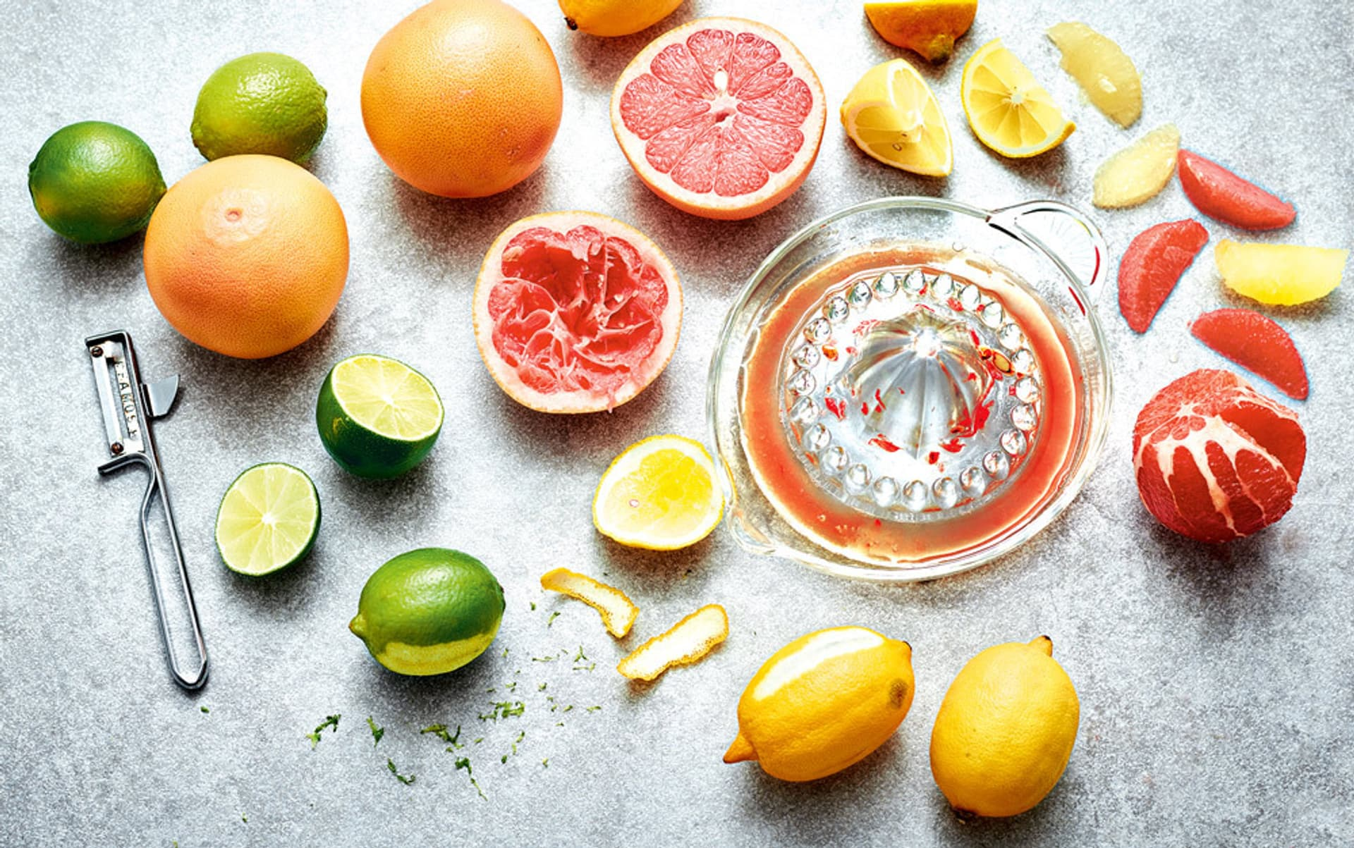 Verschiedene Arten von Zitrusfrüchten liegen auf einem hellgrauen Untergrund, manche am Stück, mache halbiert, filetiert oder ausgepresst.