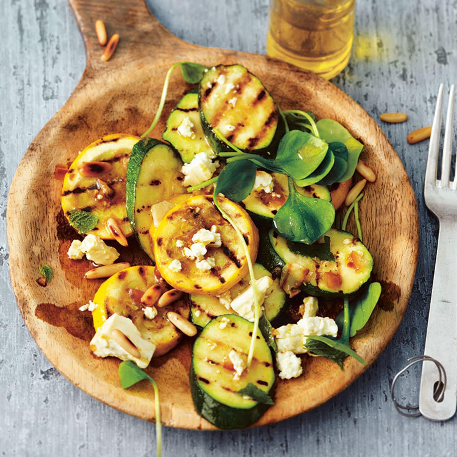 Ein Brettchen belegt mit gerösteten Zucchini und Salat