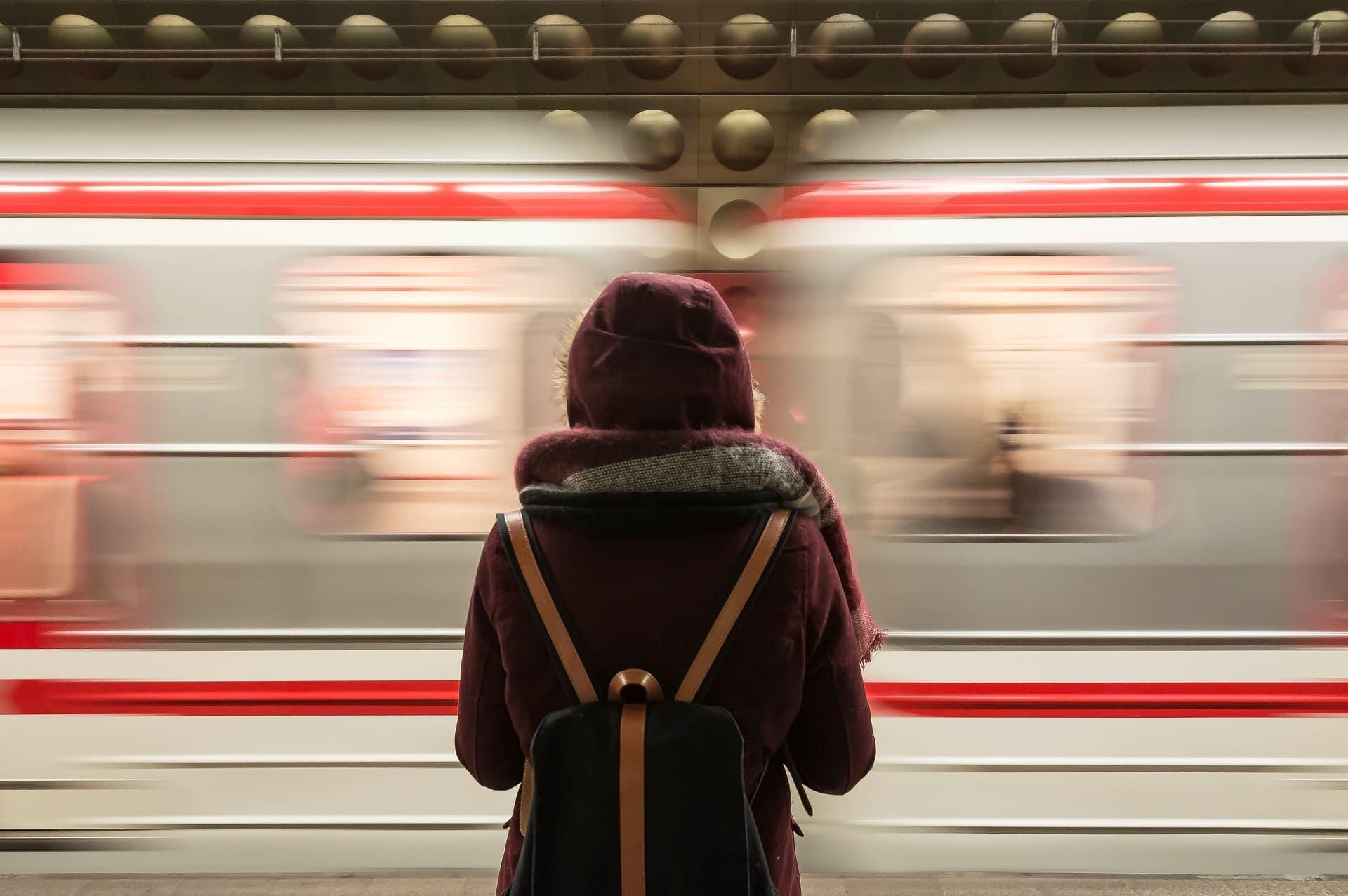 Person von hinten am Bahnsteig, im Hintergrund rauscht Zug vorbei