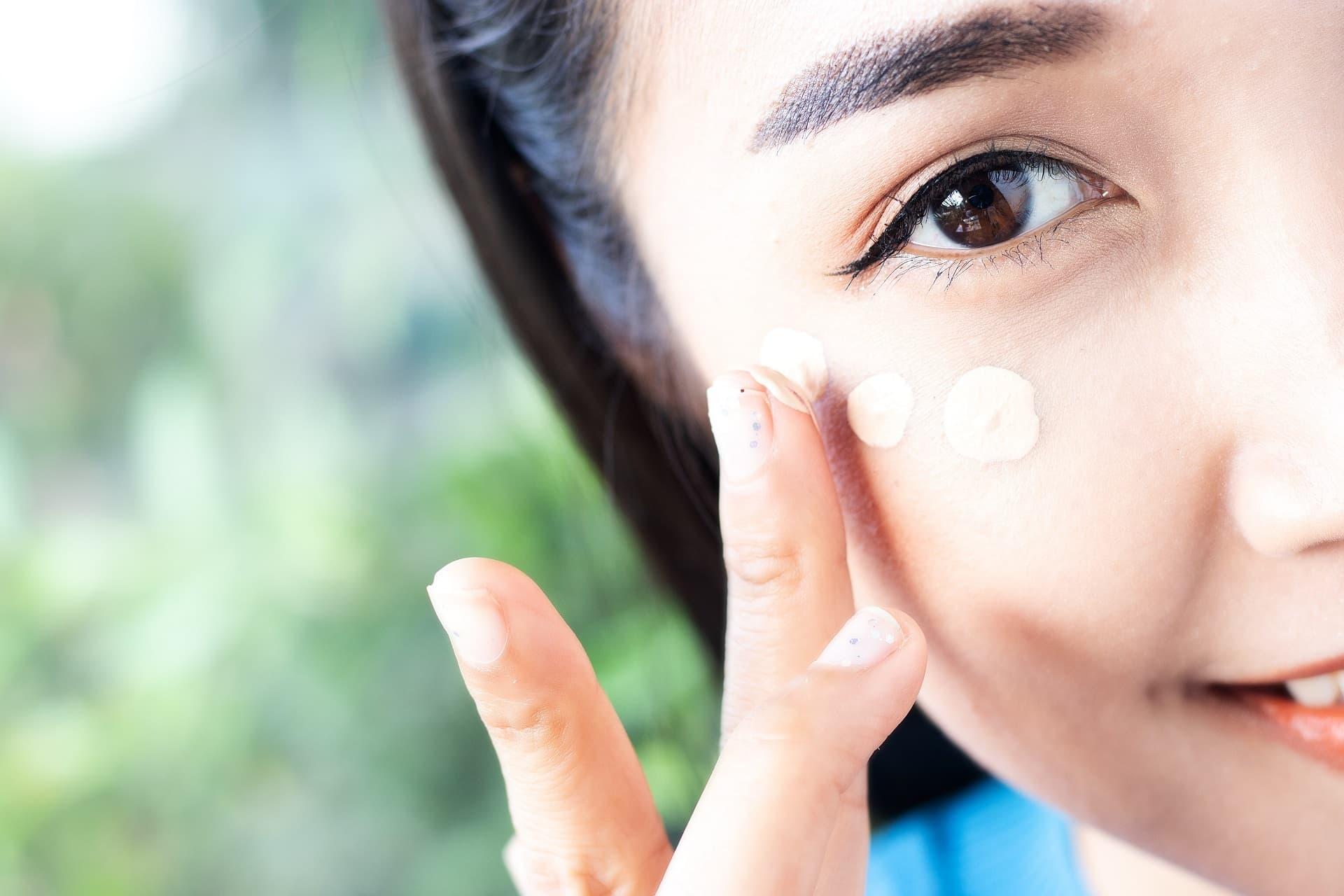 Frau trägt Concealer unter den Augen auf