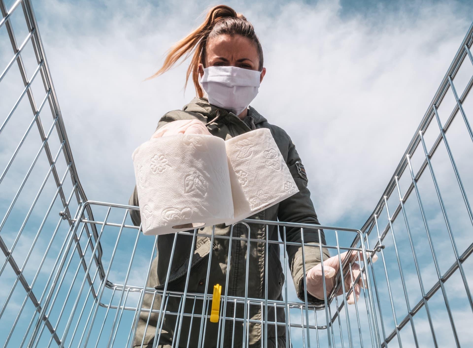 Frau mit Schutzmaske legt Toilettenpapier in Einkaufswagen