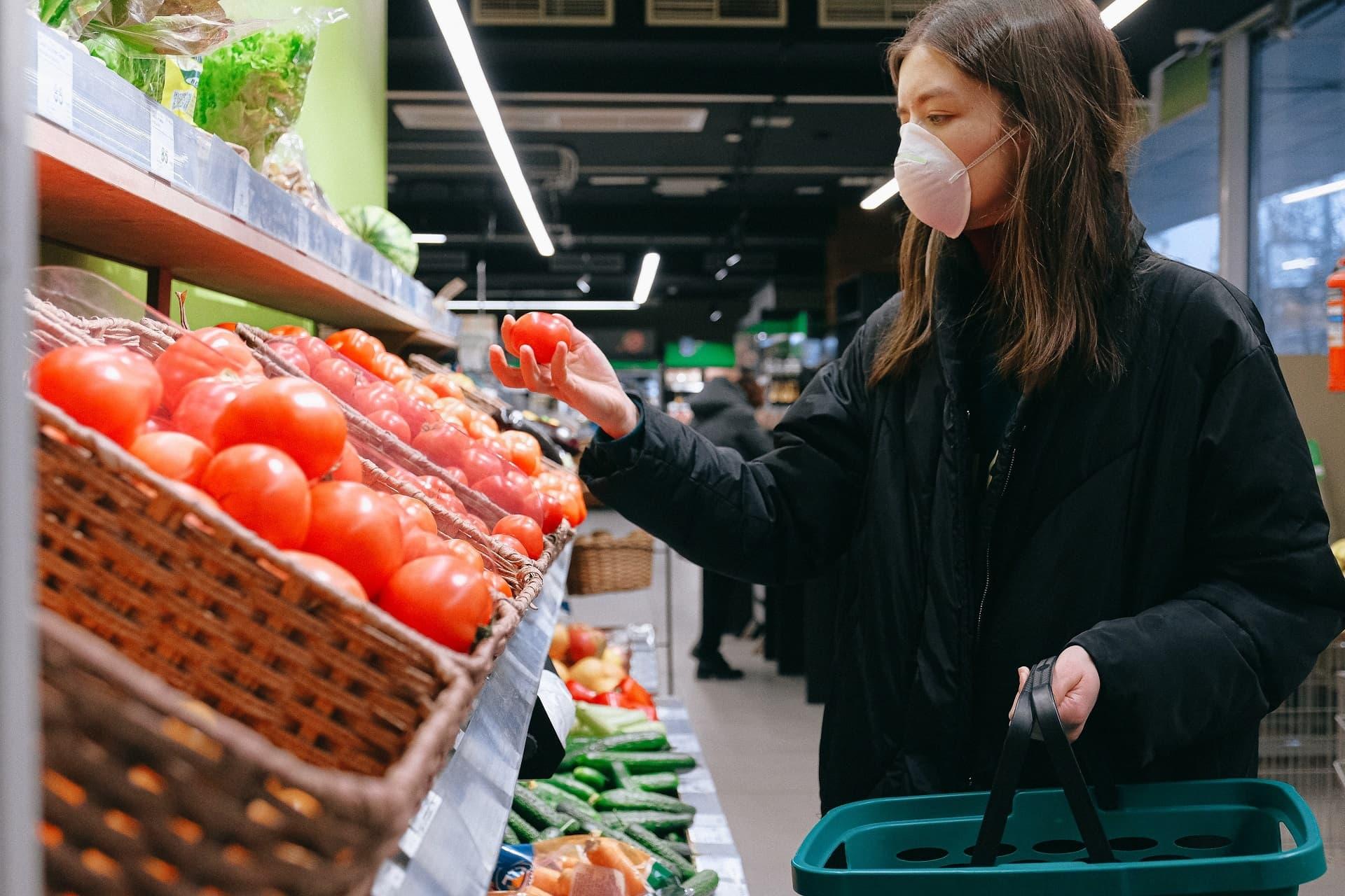Frau kauft ein mit Mund-Nasen-Schutz