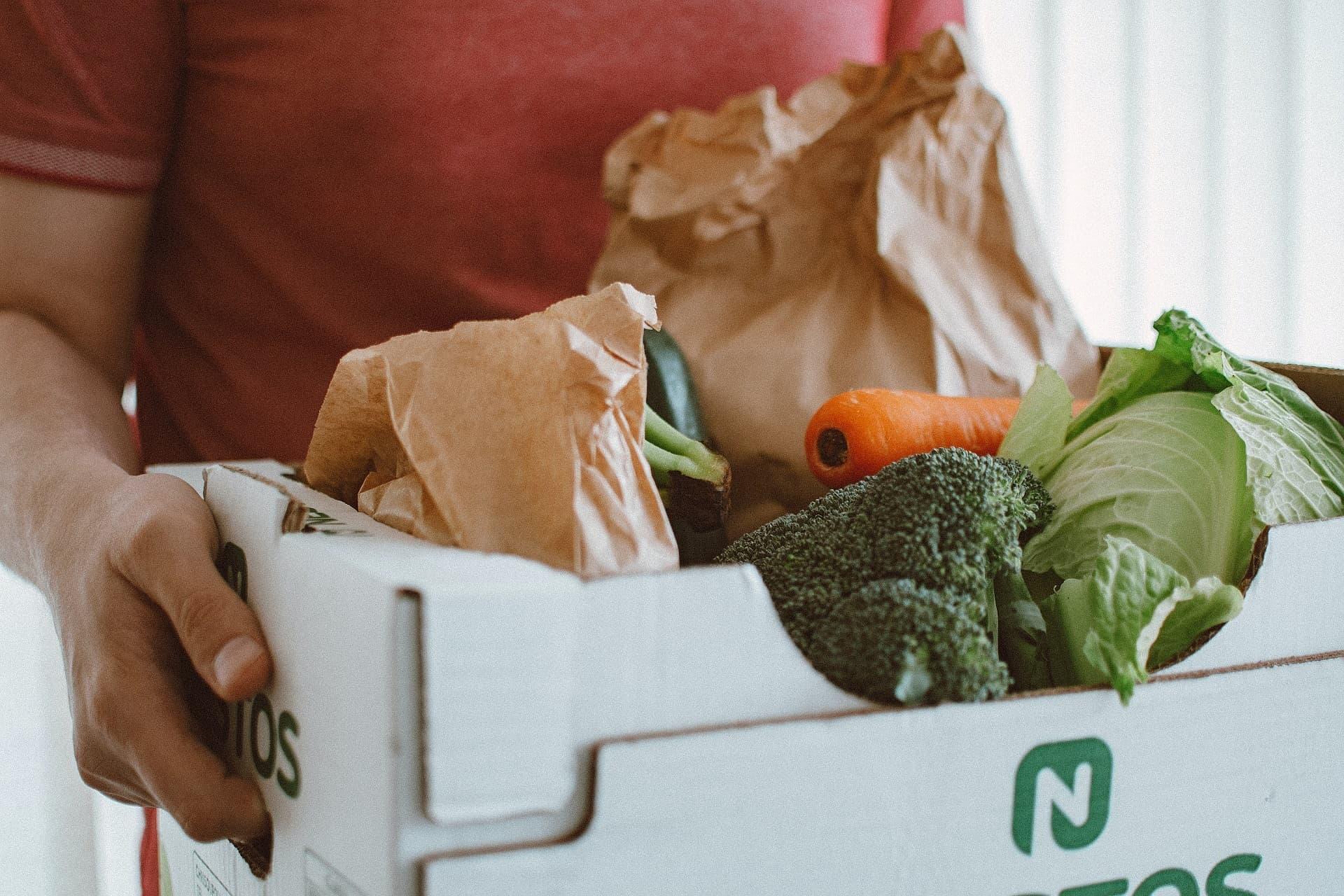 Person trägt Kiste mit Gemüse