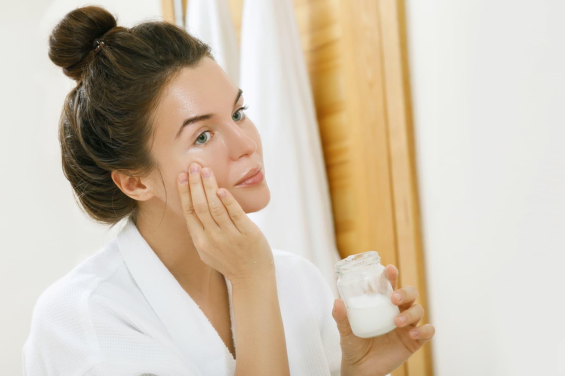 Frau cremt Gesicht mit Kokosöl ein