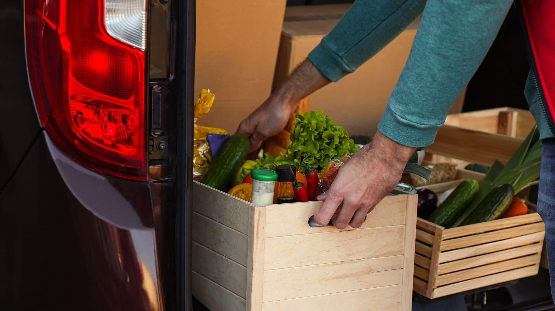 Lieferant hebt Bio-Kiste aus Kofferraum