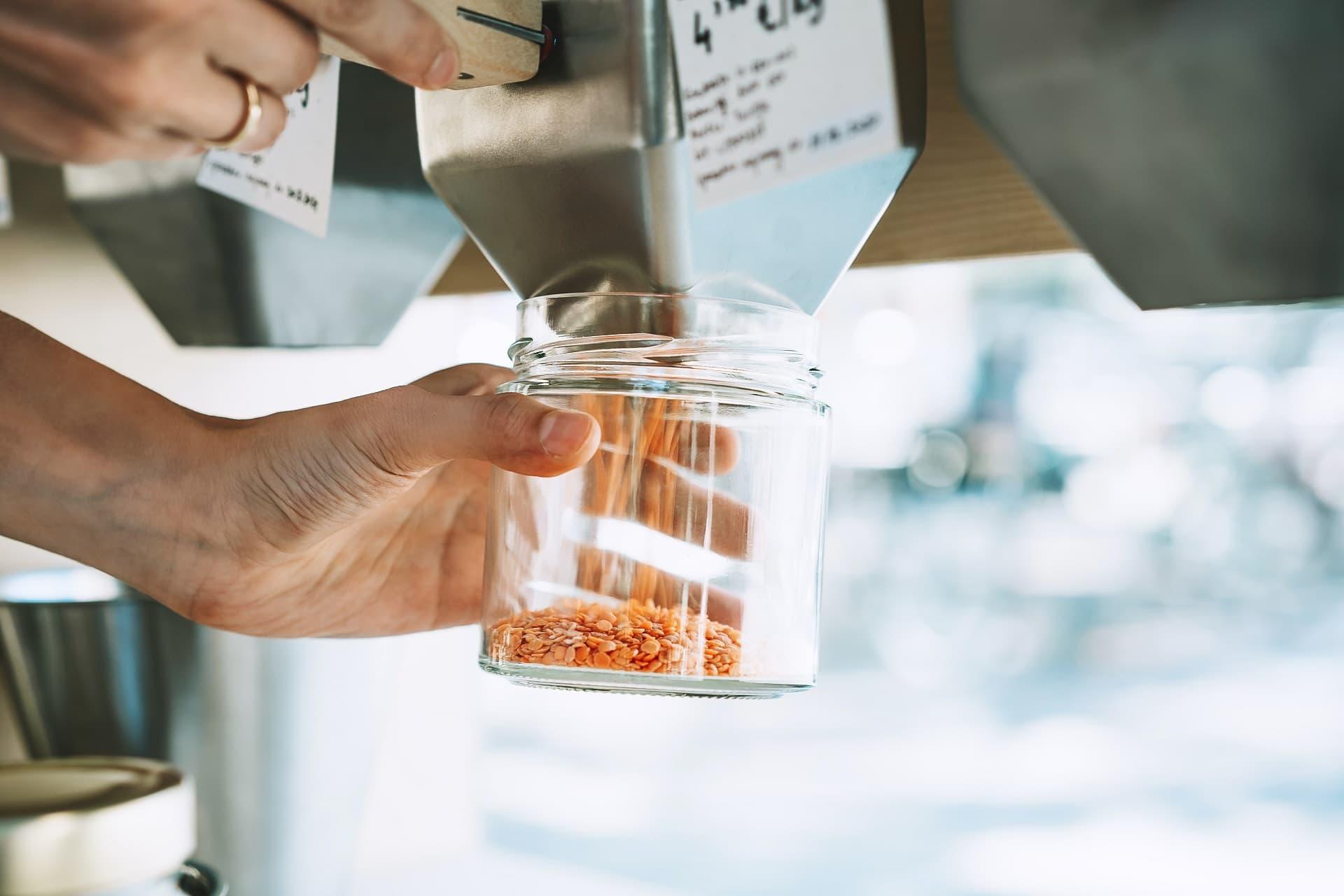 Linsen werden in ein Schraubglas abgefüllt
