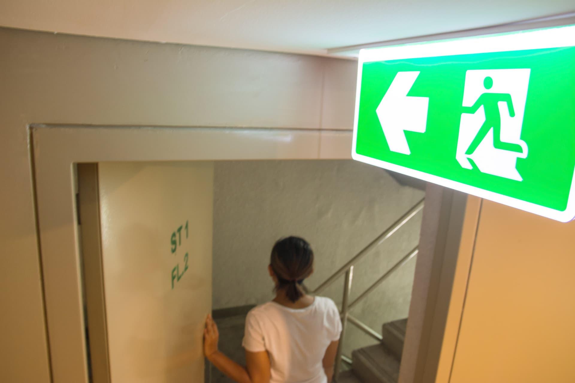 Notausgangsschild und Frau die, durch Tür geht
