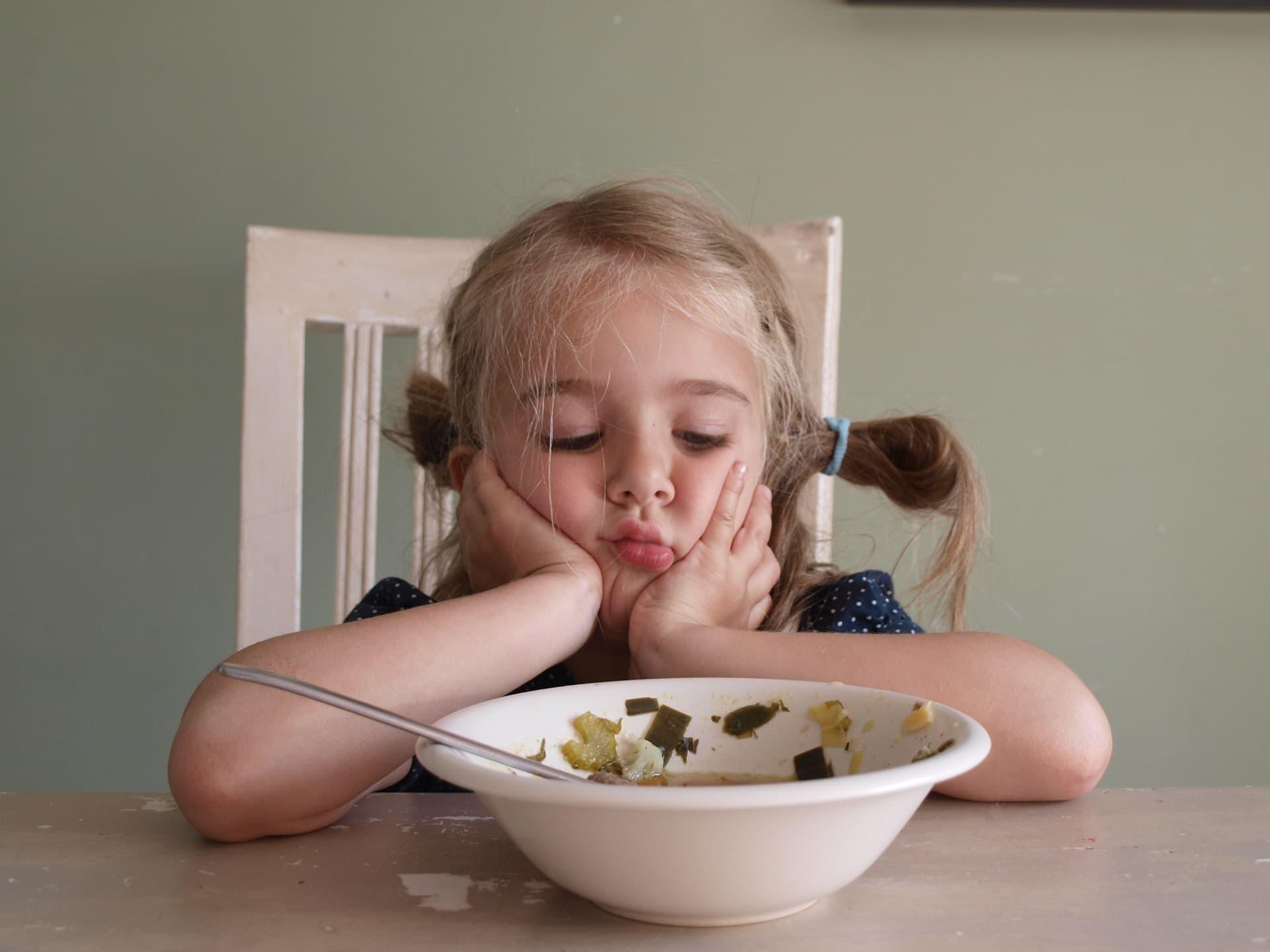 Kind vor halbvollem Teller