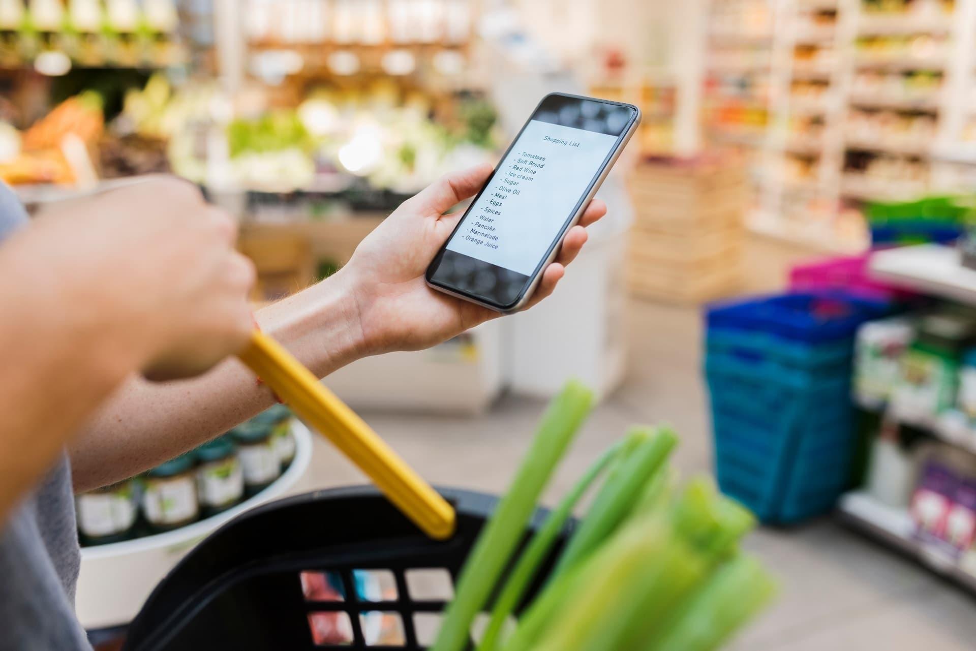 Mit Einkaufsliste auf dem SMartphone im Supermarkt