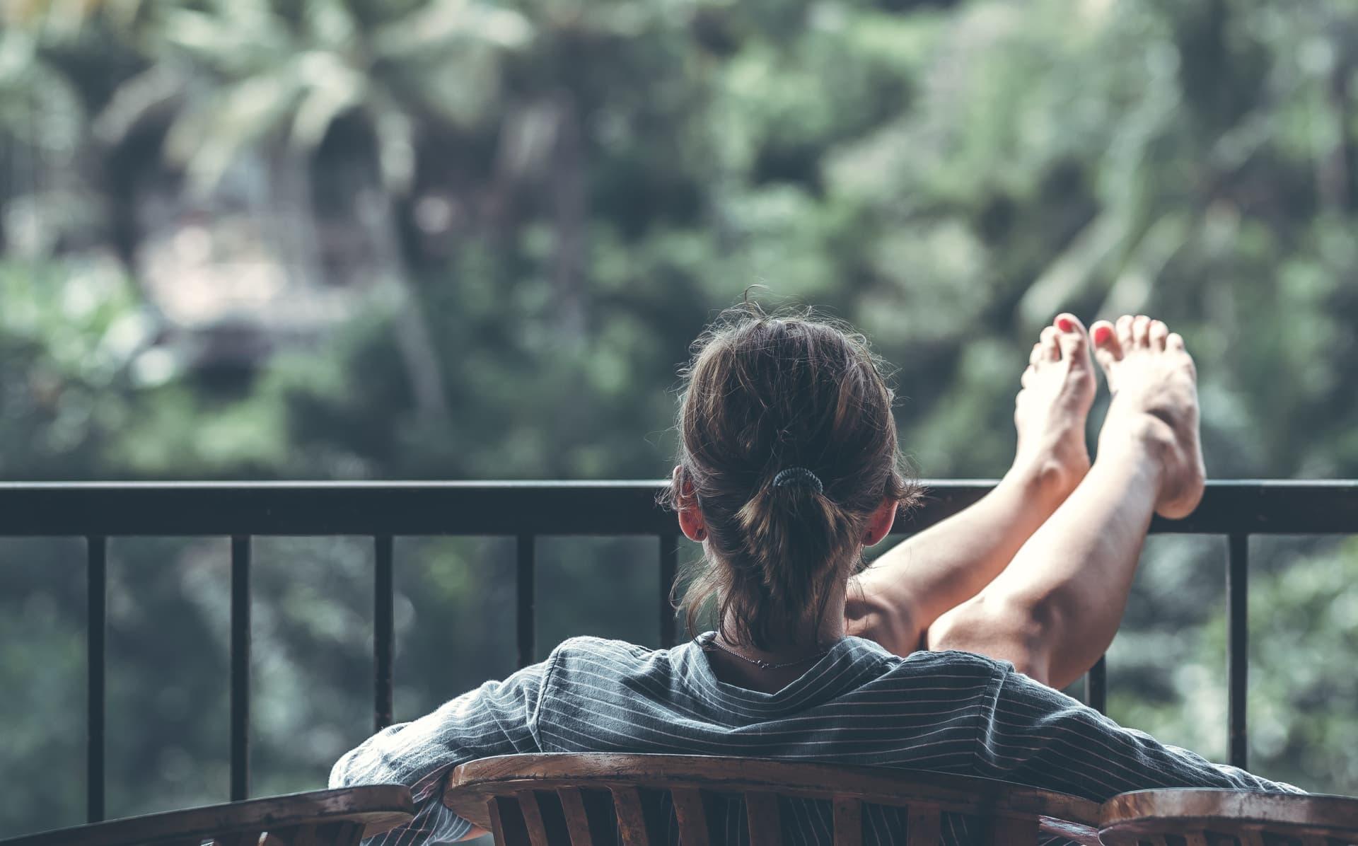 Frau auf Balkon; legt Füße hoch