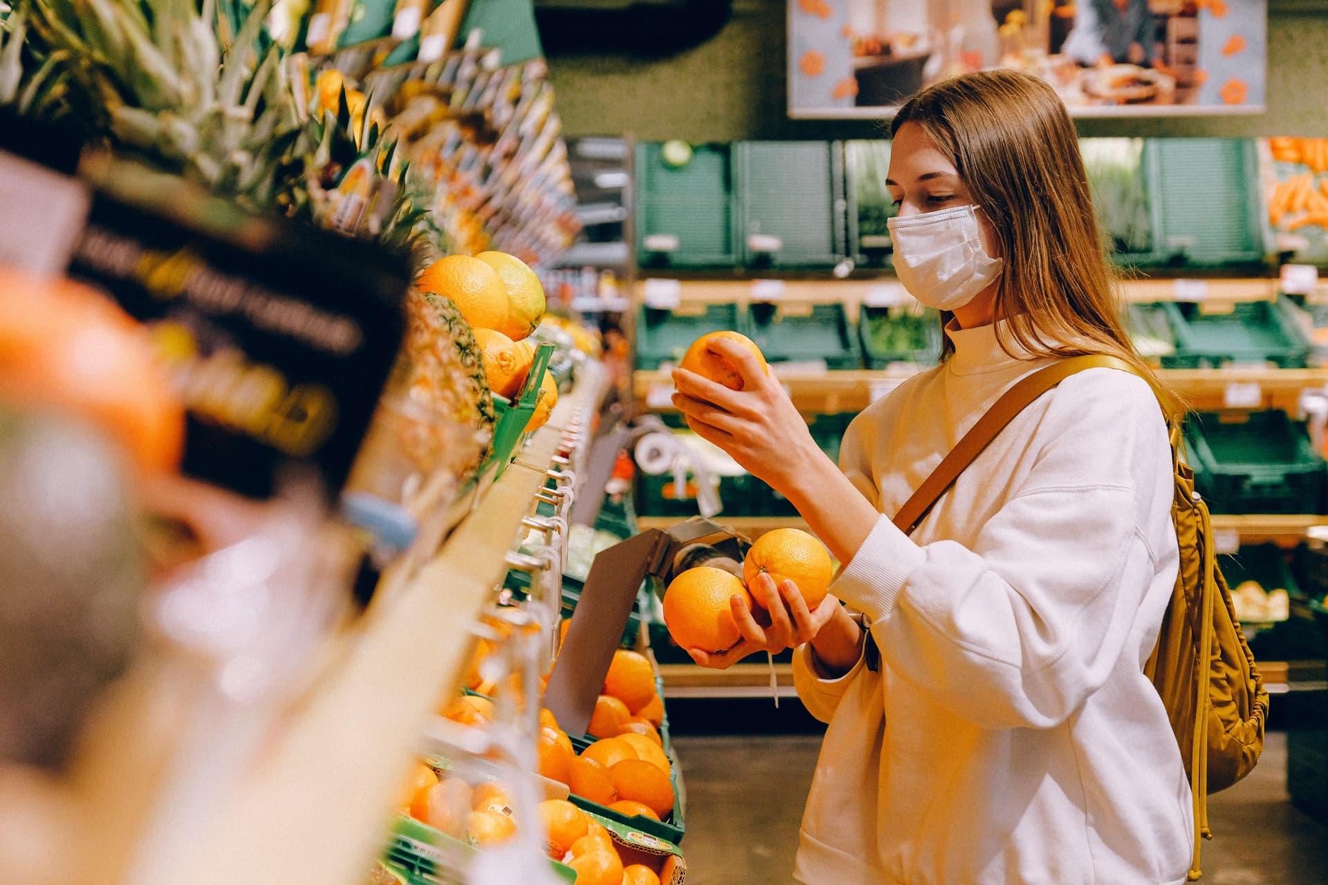 Frau mit Maske in Obstabteilung