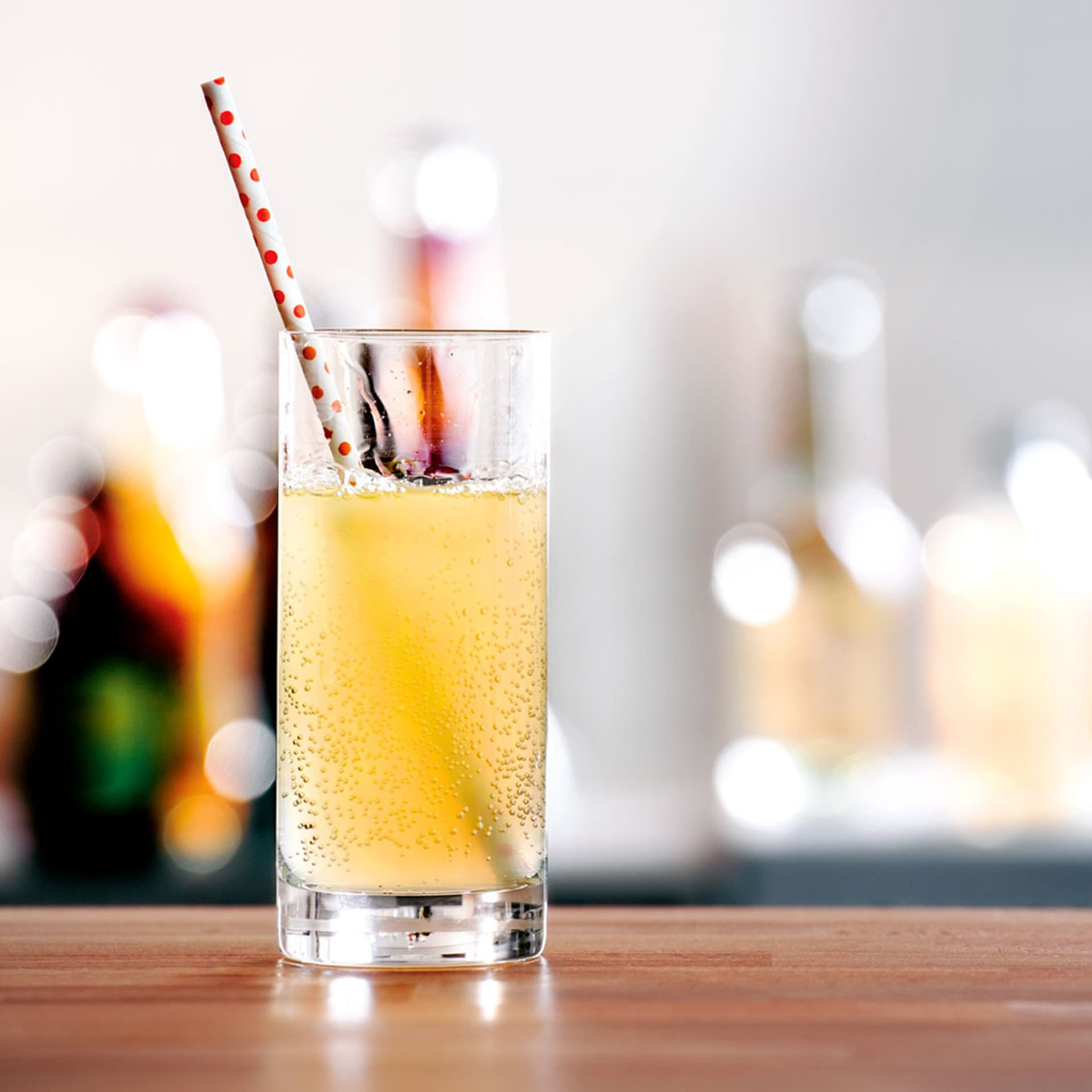 Ein Glas gefüllt mit Limonade in dem ein Strohhalm steckt.