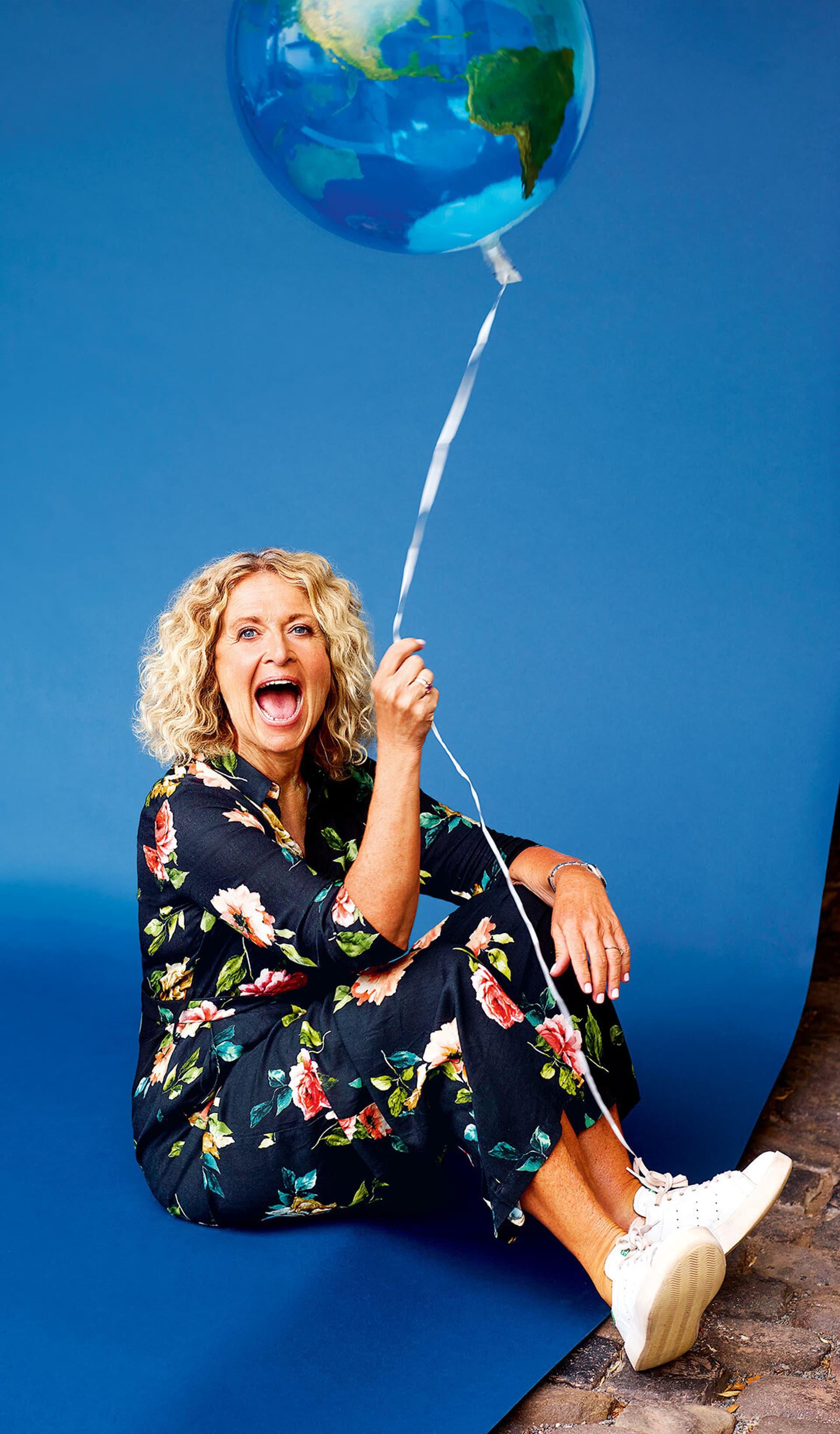 Susanne Fröhlich hält einen Luftballon in Form der Weltkugel an einer Schnur und lacht