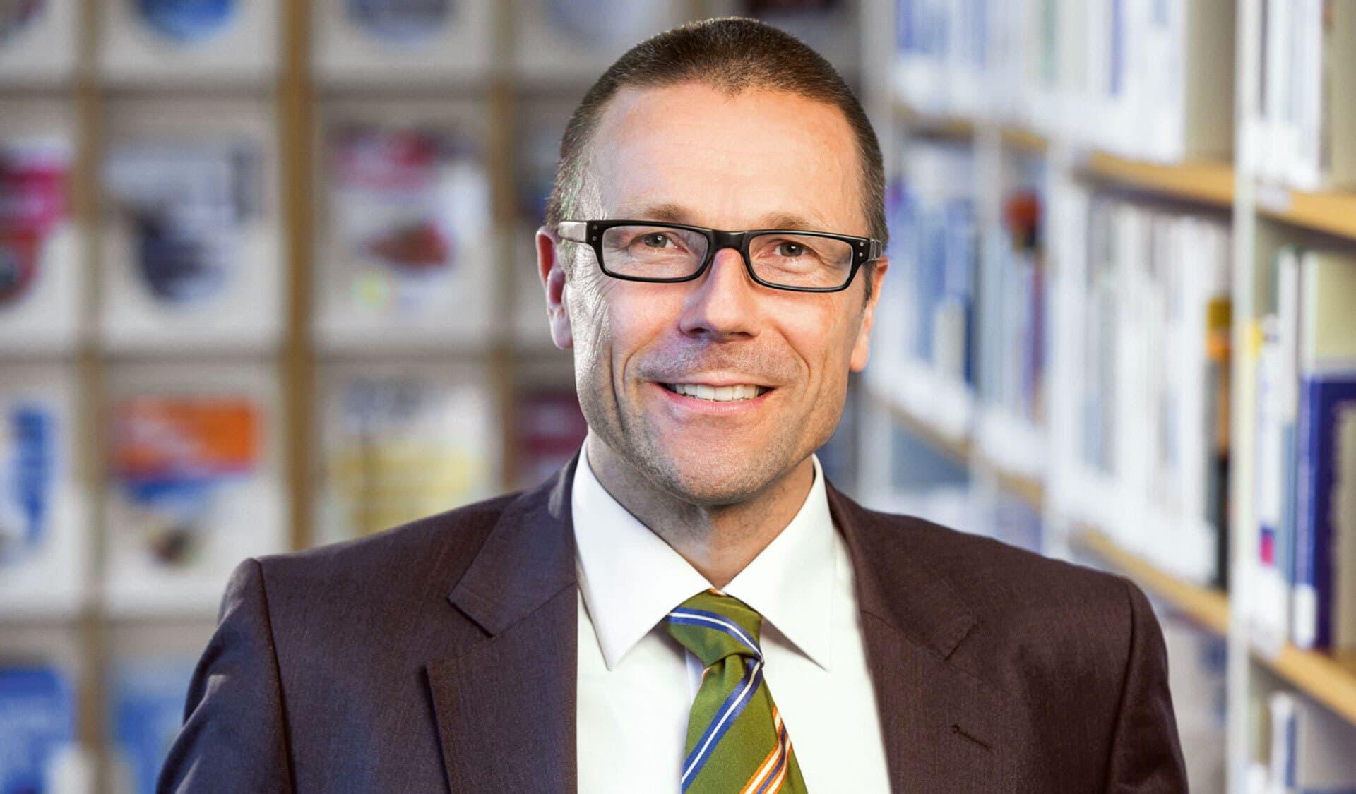 Porträtfoto von Prof. Dr. Uwe Schneidewind in Anzug und Krawatte. Er lächelt in die Kamera
