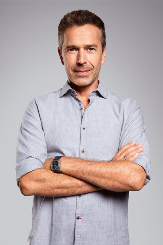 Porträt von Dirk Steffens, der in einem hellgrauen, kurzärmeligem Hemd mit verschränkten Armen und einem leichten Lächeln vor einem hellen Hintergrund steht.