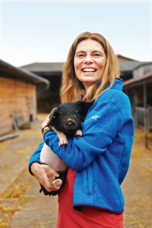 Sarah Wiener trägt eine azurblaue Sportjacke und hält ein kleines schwarz geflecktes Schwein im Arm. Beide gucken in die Kamera. Im Hintergrund sieht man die Umrisse eines Bauernhofs.