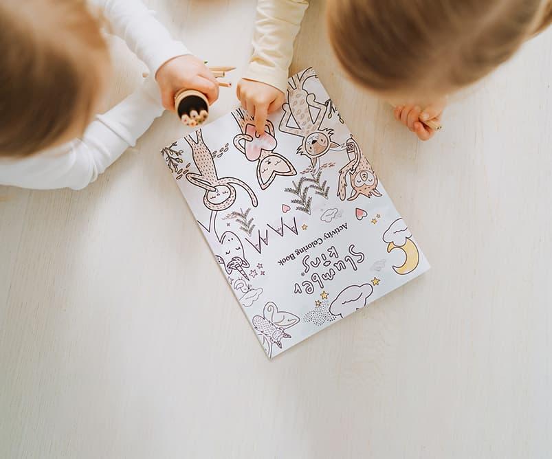 Children coloring a Slumberkins coloring page