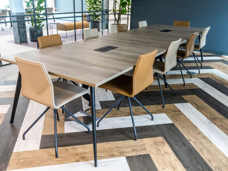 close up profile shot of meeting room table caramel leather chairs and patterned wooden floor