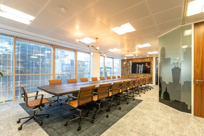 Long boardroom table with caramel leather chairs, bark wall and manifestation