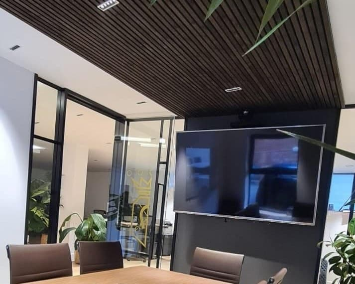 meeting room with dark wood soundproofing panels on ceiling